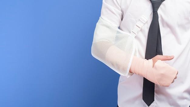 Młody biznesmen z rannym ramieniem w temblaku na niebieskiej ścianie