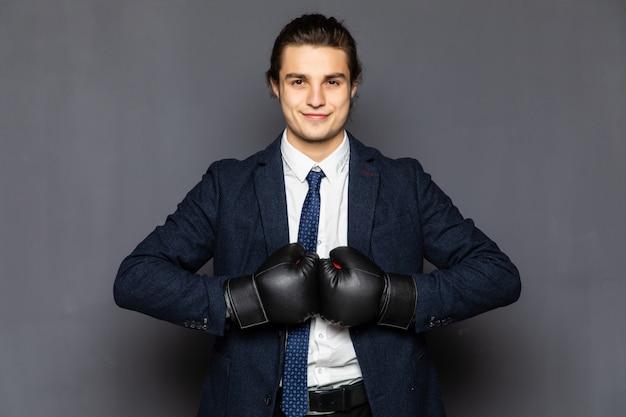 Młody biznesmen z rękawice bokserskie na białym tle