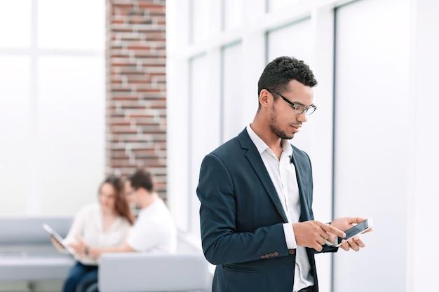 Młody biznesmen z smartphone stojący w pobliżu okna biura. ludzie i technologia