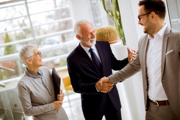 Młody biznesmen z starszymi klientami stoi w biurze