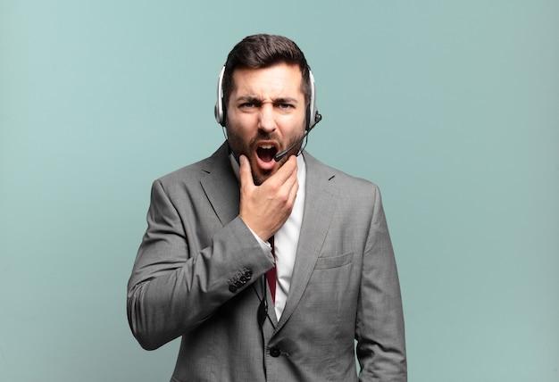 Młody biznesmen z szeroko otwartymi ustami i oczami i ręką na brodzie