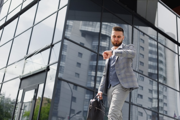 Młody biznesmen z teczką uruchomiony na ulicy miasta na tle nowoczesnego biurowca
