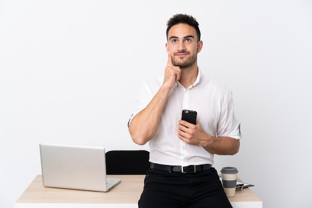 Młody biznesmen z telefonem komórkowym w miejscu pracy myśli pomysł