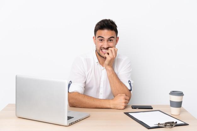 Młody biznesmen z telefonem komórkowym w miejscu pracy nerwowy i przestraszony