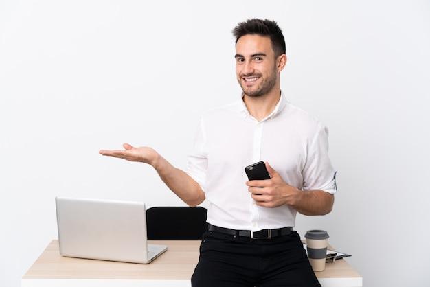 Młody biznesmen z telefonem komórkowym w miejscu pracy, rozkładając ręce na bok za zaproszenie