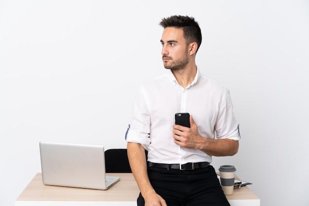 Młody biznesmen z telefonu komórkowego w miejscu pracy patrząc po stronie