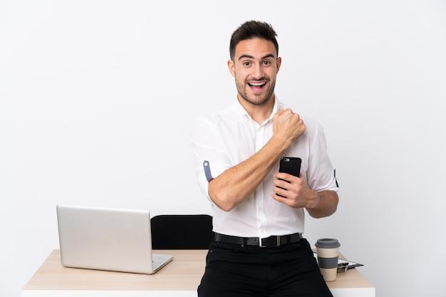 Młody biznesmen z telefonu komórkowego w miejscu pracy świętuje zwycięstwo