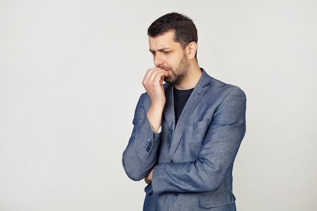 Młody biznesmen z uśmiechem, mężczyzna z brodą w kurtce, wygląda na spiętego i nerwowego, z rękami na ustach, obgryzając paznokcie. problem lęku.