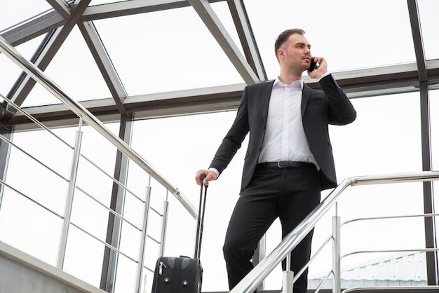 Młody biznesmen z walizką w stylowym garniturze rozmawia przez telefon podczas spaceru po schodach w nowoczesnym budynku biznesowym
