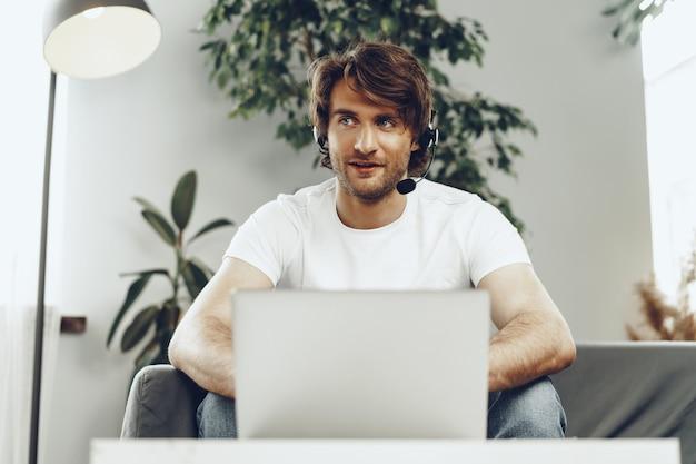Młody biznesmen z zestawu słuchawkowego pracuje na laptopie w domu