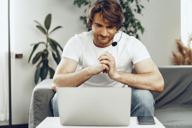 Młody biznesmen z zestawu słuchawkowego pracuje na laptopie