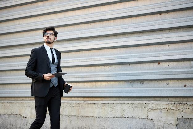 Młody biznesmen za pomocą komputera typu tablet poza ubrany w klasyczny garnitur