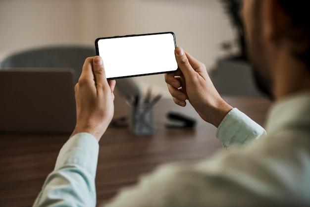 Młody biznesmen za pomocą telefonu komórkowego