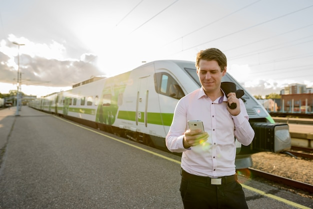 Młody biznesmen zadowolony uśmiechając się i używając telefonu komórkowego przed pociągiem na stacji kolejowej