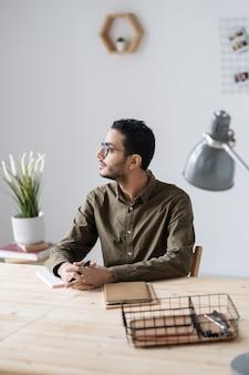 Młody biznesmen zamyślony w casual, siedząc przy drewnianym stole w biurze podczas planowania pracy na cały dzień