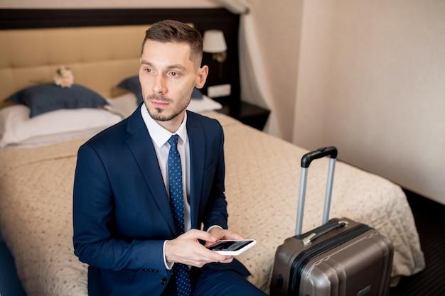 Młody biznesmen zamyślony w wizytowym przy użyciu smartfona, siedząc na łóżku w pokoju hotelowym przed wyjściem