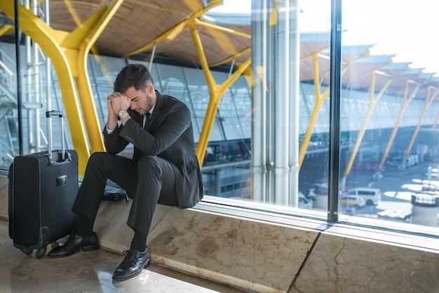 Młody biznesmen zdenerwowany na lotnisku, czekając na opóźniony lot z bagażem