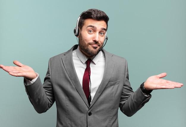 Młody biznesmen zdziwiony i zdezorientowany, wątpiący, ważący lub wybierając różne opcje z koncepcją telemarketingu z zabawnym wyrazem