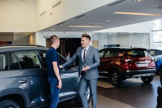 Młody biznesmen ze sprzedawcą patrzy na nowy samochód w salonie samochodowym. kupowanie samochodu.