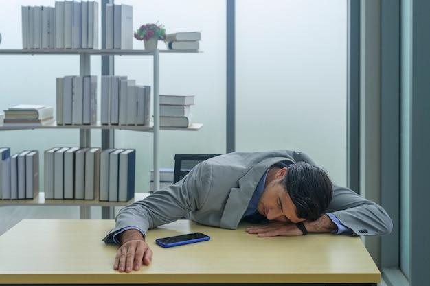Młody biznesmen zmęczony i wyczerpany w miejscu pracy.