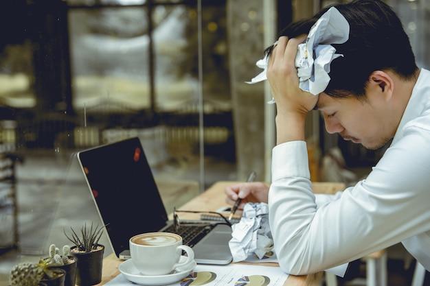 Młody biznesmen zmiażdżył papier ze stresem.