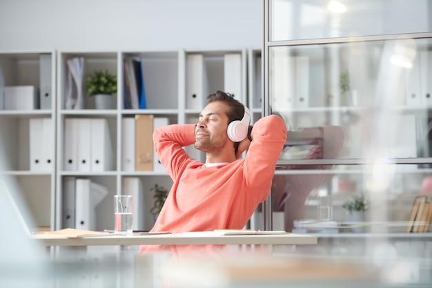 Młody biznesmen zrelaksowany słuchania muzyki w słuchawkach siedząc przy biurku w biurze
