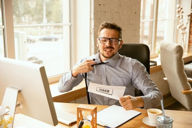 Młody biznesmen zwolniony, wygląda na zdenerwowanego