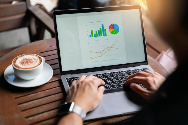 Młody biznesmena działanie tworzy mapę na laptopie i pije gorącą kawę