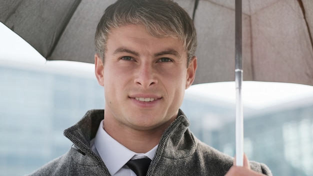 Młody biznesmena mienia parasol i używać mądrze telefon w deszczowym dniu.
