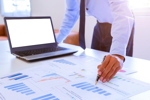 Młody biznesmena mienia pióro wskazuje wykres i mapa w biurze.