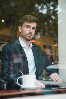 Młody biznesmena obsiadanie w kawiarni z laptopem