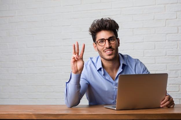 Młody biznesowego mężczyzna obsiadanie i działanie na laptopie pokazuje liczbę trzy, symbol liczenie, pojęcie matematyka, ufny i rozochocony