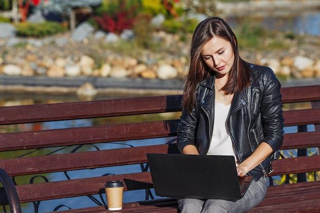 Młody biznesowej kobiety obsiadanie i działanie w parku z laptopem