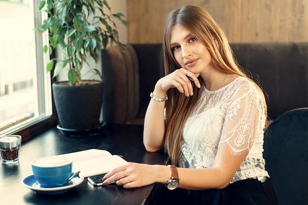 Młody biznesowej kobiety obsiadanie przy stołem w sklep z kawą i robić notatkom