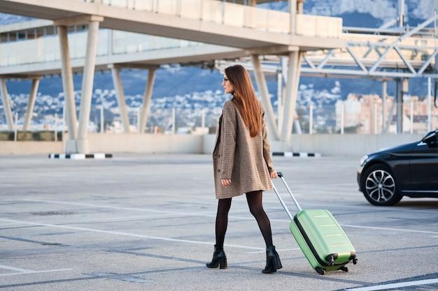 Młody biznesowej kobiety odprowadzenie przeciw czarnemu luksusowemu samochodowi na tle.