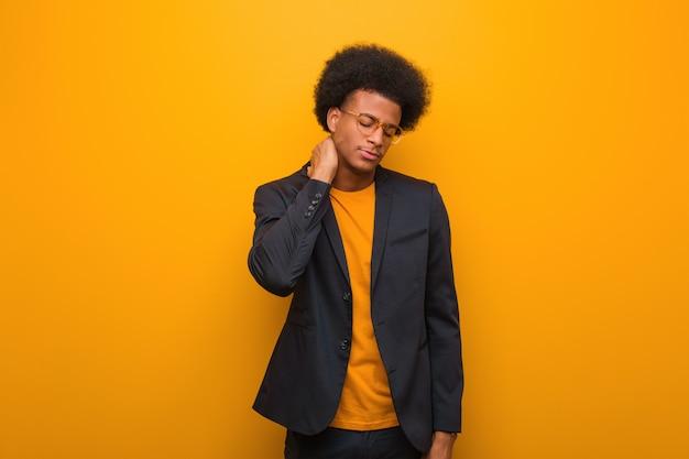 Młody biznesowy amerykanina afrykańskiego pochodzenia mężczyzna nad pomarańczową ścianą cierpi ból szyi