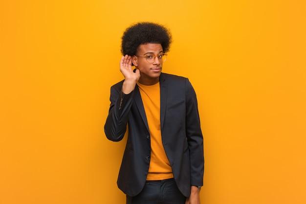 Młody biznesowy amerykanina afrykańskiego pochodzenia mężczyzna nad pomarańczową ścianą próbuje słuchać plotki