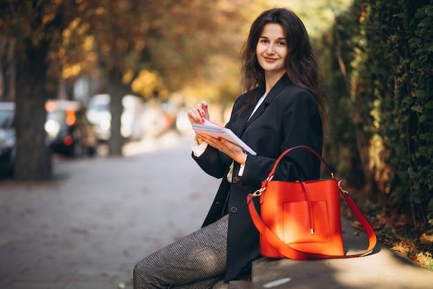 Młody biznesowy damy czytanie w parku