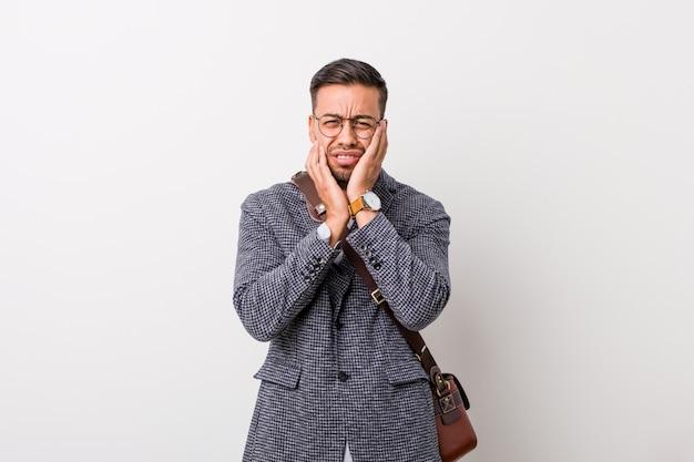 Młody biznesowy filipiński mężczyzna na białej ścianie jęczy i płacze niepocieszony.