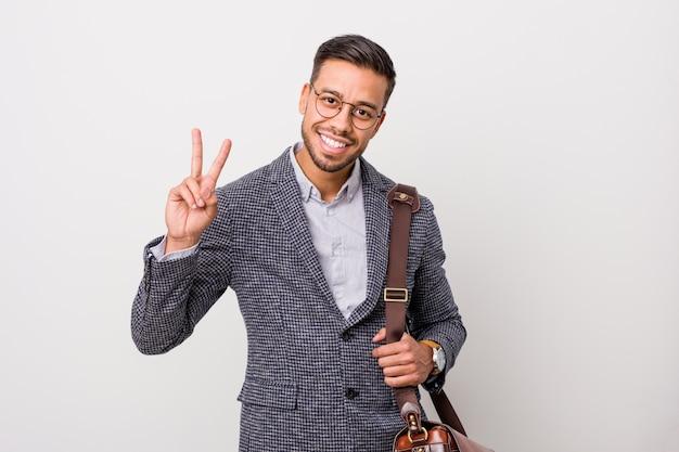 Młody biznesowy filipiński mężczyzna przeciw białej ścianie pokazuje zwycięstwo znaka i ono uśmiecha się szeroko.