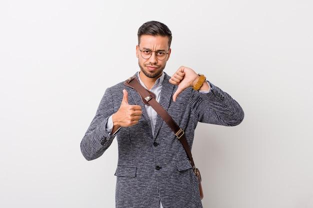Młody biznesowy filipiński mężczyzna przy białej ścianie pokazuje kciuki w górę i kciuki w dół, trudny wybór