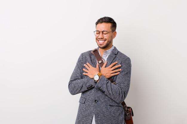 Młody biznesowy filipiński mężczyzna śmia się utrzymujący ręki na sercu przeciw białej ścianie, pojęcie szczęście.