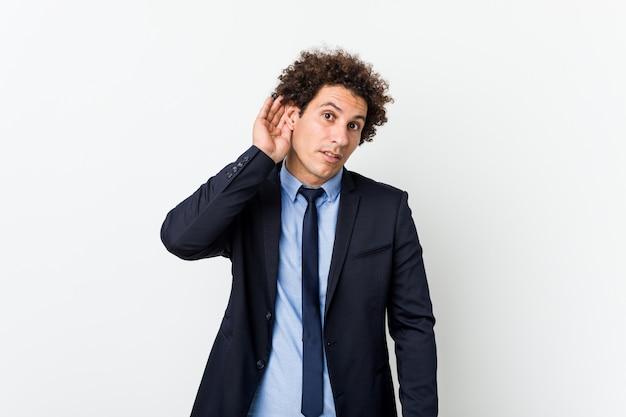 Młody biznesowy kędzierzawy mężczyzna próbuje słuchać plotki przeciw białemu tłu.