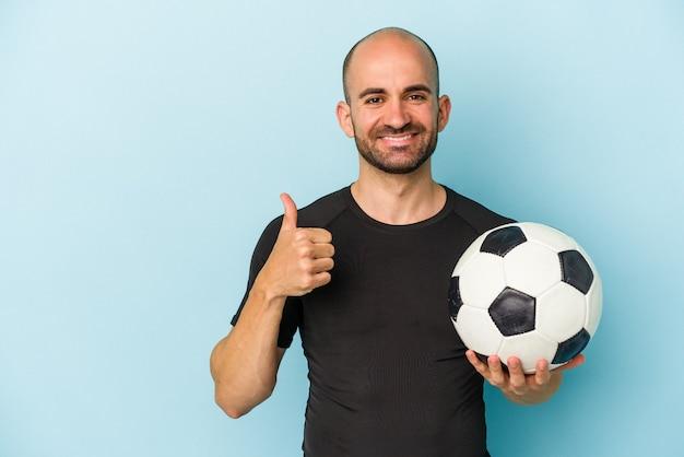 Młody biznesowy łysy mężczyzna grający w piłkę nożną na białym tle na niebieskim tle uśmiechający się i podnoszący kciuk w górę