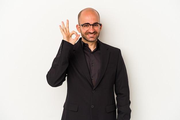 Młody biznesowy łysy mężczyzna odizolowywający na białym tle wesoły i pewny siebie pokazując ok gest.