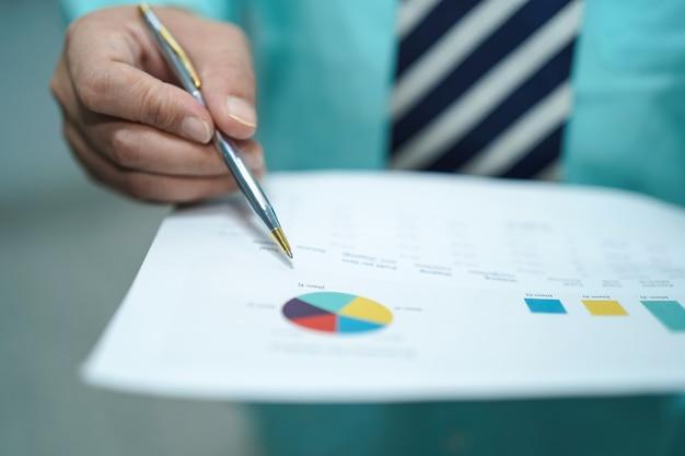 Młody biznesowy mądrze kierownik pracuje z nowym sukcesu początkowym projektem analizuje wykresu plan.