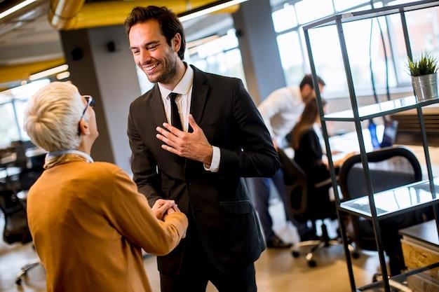 Młody biznesowy mężczyzna i starsza biznesowa kobieta trząść ręki w biurze