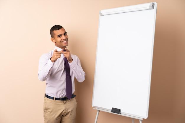 Młody biznesowy mężczyzna nad odosobnioną ścianą daje prezentaci na białej desce i wskazuje palec przy tobą