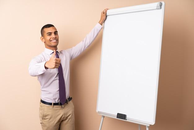 Młody biznesowy mężczyzna nad odosobnioną ścianą daje prezentaci na białej desce z kciukiem up
