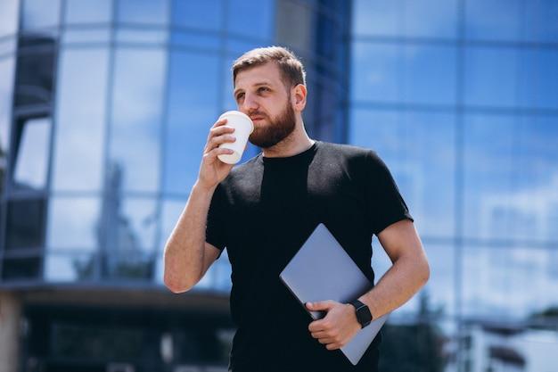 Młody biznesowy mężczyzna pije kawę z laptopem